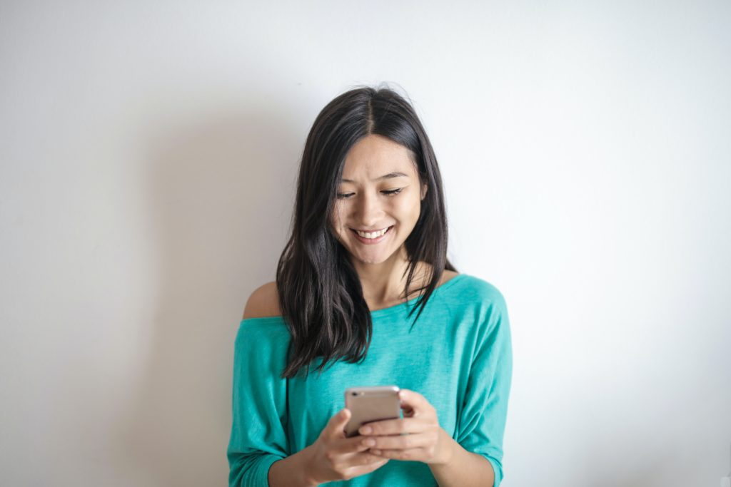 Young woman looking at her iphone and smiling